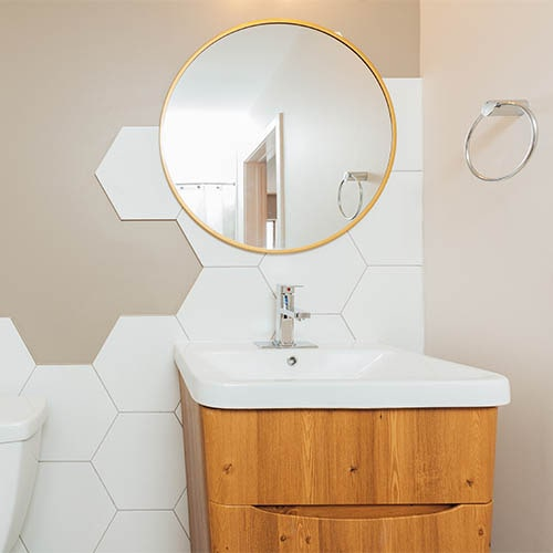 brown bathroom vanity with white sink and gold circular mirror