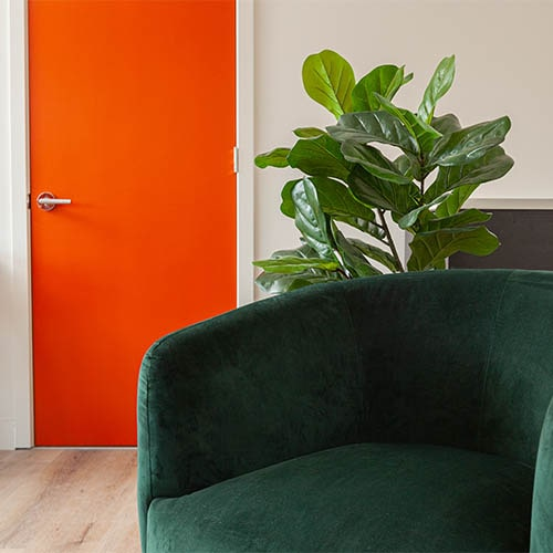 green chair in foreground with orange entrance door in background